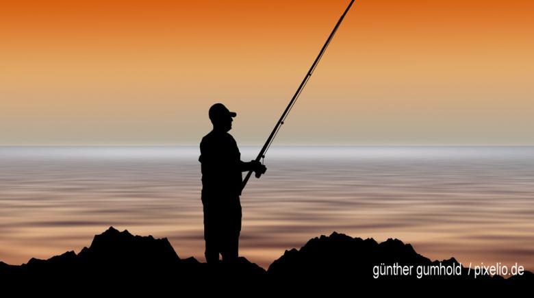 Fischer mit Angel im Sonnenuntergang
