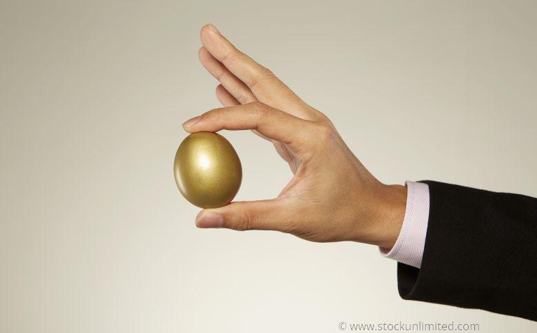 Hand hält goldenes Ei