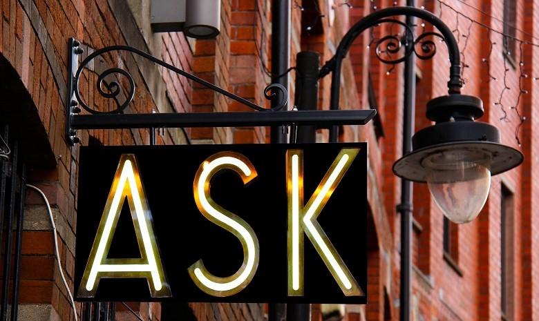 """Ansicht eines schwarzen Schildes mit der Aufschrift """"Ask"""", als Anspielung auf die sieben W-Fragen des Journalismus"""