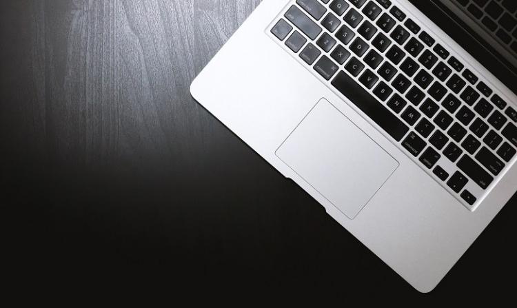 """Ansicht einer silberfarbenen Computertastatur auf einem dunklen Tisch als Headerbild für den Beitrag """"Gute Texte schreiben"""""""