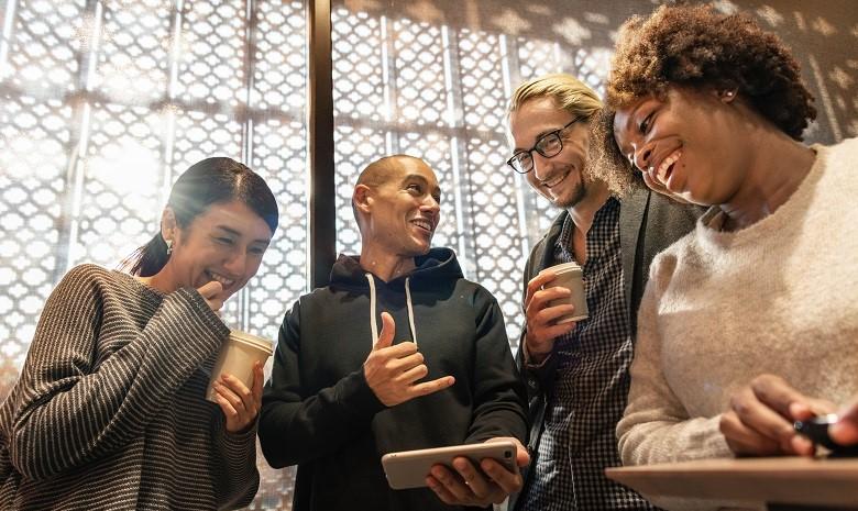 Bild einer Gruppe von lachenden Menschen um ein Smartphone gruppiert, als Illustration zum Thema gute Webtexte schreiben und Emotionen erzeugen