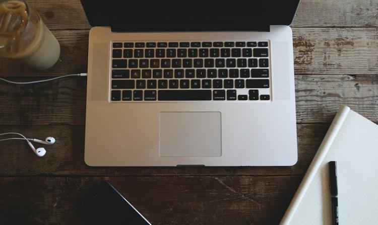 Foto eines Laptops und Notizbuchs