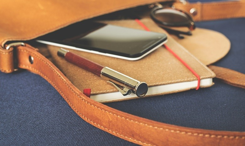 Nahaufnahme eines Notizbuchs, stifts und Handys in einer Ledertasche als Illustration für den Abschnitt zu Pressemeldungen