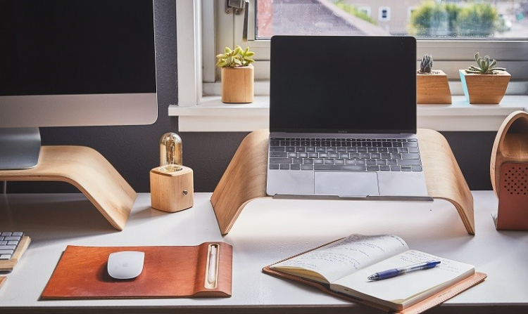 Ansicht eines Schreibtisches mit Laptop, Maus und Notizbuch als Headerbild für den Artikel zu Textgattungen unterscheiden und schreiben