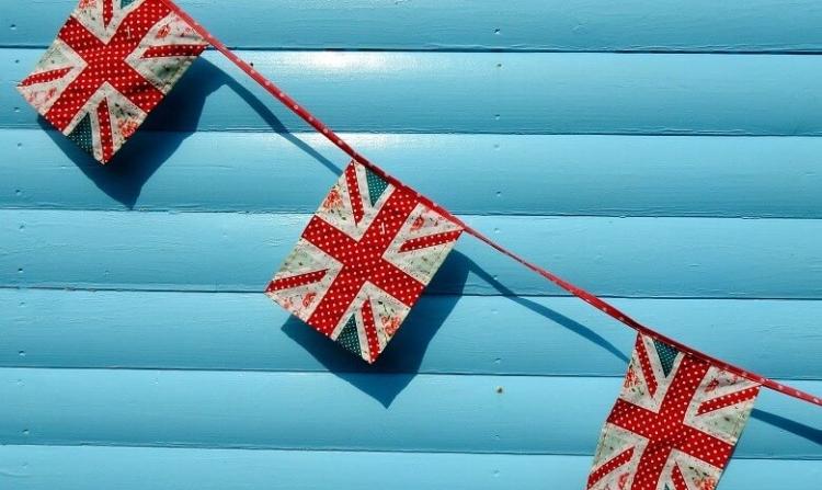Ein Band mit selbst genähten britischen Flaggen ist vor einem blauen Hintergrund gespannt.