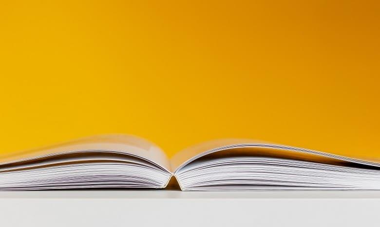 Synonyme finden Beitragsbild 1: Ansicht eines aufgeschlagenen Buches vor gelbem Hintergrund