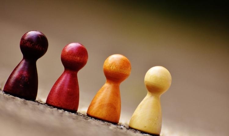 Synonyme finden Headerbild: Vier gleich geformte Spielfiguren in verschiedenen Farben stehen in einer Reihe.