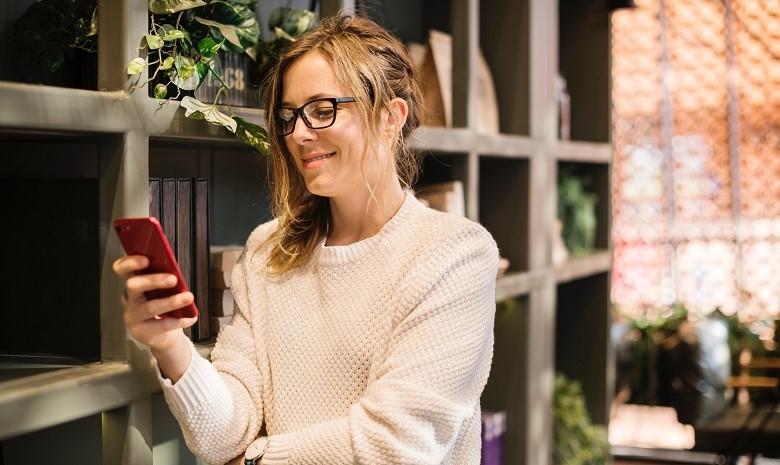 Headline Text Beitragsbild 1: Eine junge Frau liest einen Artikel auf ihrem Smartphone.