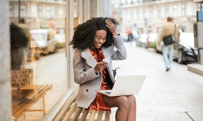 Headline Texte Beitragsbild 2: Eine junge Frau lacht über einen Beitrag, den sie auf ihrem Smartphone liest