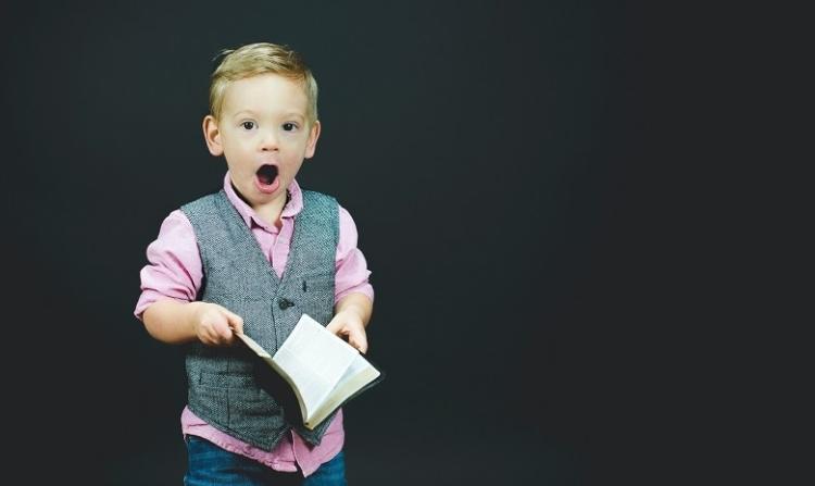 Headline Texte Headerbild: Ein kleiner Junge schaut überrascht in die Kamera