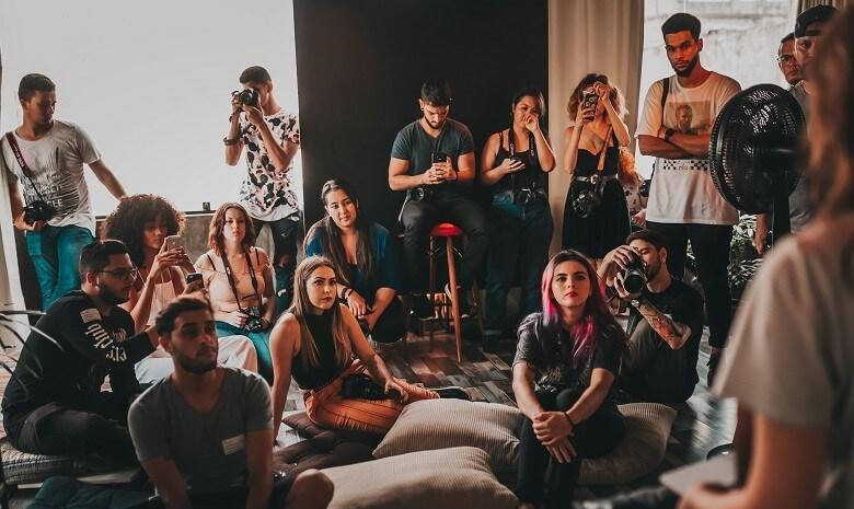 Beitragsbild 1 Rede schreiben: Eine bunt gemischte Gruppe an Menschen sitzt auf Hockern und Kissen und hört gebannt einer Rednerin zu.