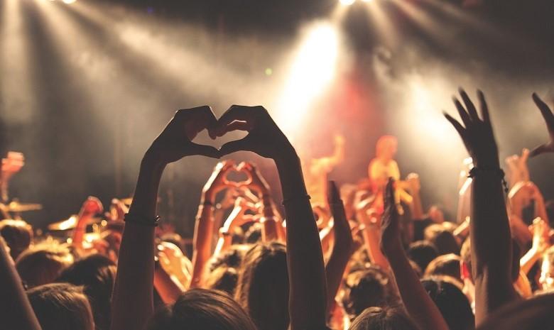 Beitragsbild 2 Rede schreiben: Foto eines Publikums, eine junge Person hält die Hände hoch und formt mit ihren Fingern ein Herz.