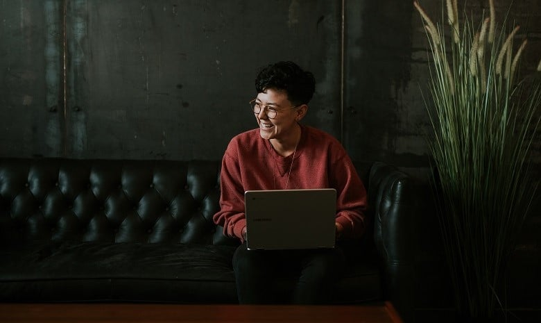 Aktive Sprache Beitragsbild 3: Eine junge, lachende Person auf dem Sofa mit Laptop