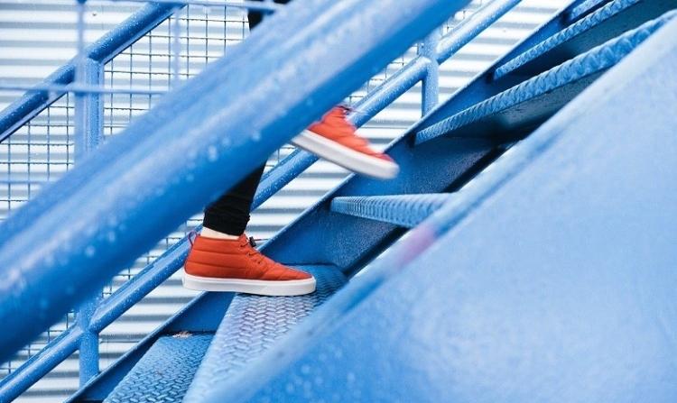 Aktive Sprache Headerbild: Person mit orangefarbenen Schuhen läuft eine Metalltreppe hoch. Nur die Beine und Füße sind zu sehen.