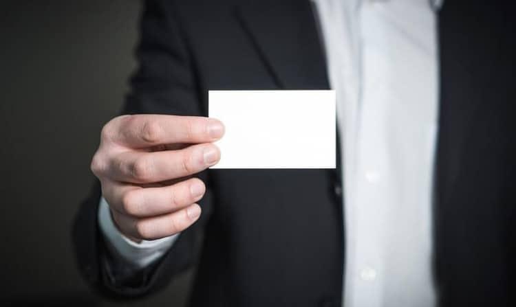 Ein Mann im Anzug hält eine Visitenkarte ins Bild