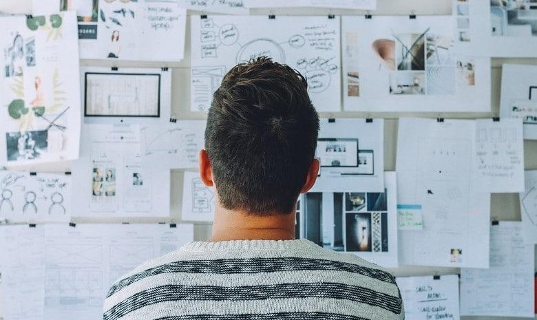 Beitragsbild Briefings verstehen 1: Ein junger Mann steht mit dem Rücken zur Kamera vor einer Wand voller Pläne und Notizen.