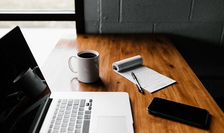 Beitragsbild Briefings verstehen 3: Draufsicht eines Schreibtischs mit Computer und einem Block mit einer Liste