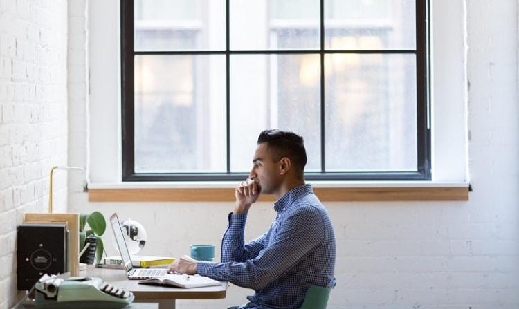 Headerbild Briefings verstehen: Ein junger Mann sitzt konzentriert an seinem Schreibtisch.