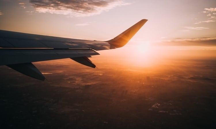 Blick aus dem Fenster eines Flugzeugs bei Sonnenaufgang