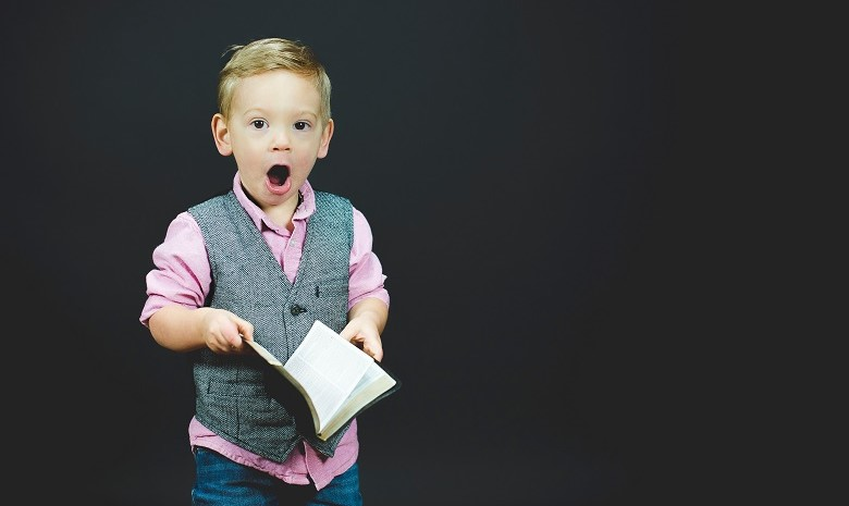Rezension schreiben Beitragsbild 2: Ein überrascht in die Kamera schauender Junge mit einem aufgeschlagenen Buch