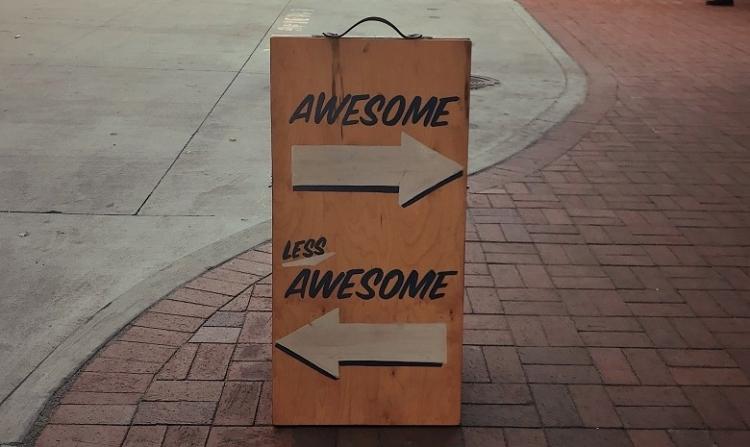 """Rezension schreiben Headerbild: Ein aufstellbares Schild mit zwei Pfeilen in verschiedene Richtungen; über dem oberen Pfeil steht die Aufschrift """"Awesome"""", über dem unteren """"Less Awesome"""""""