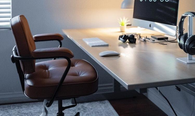 Ein gemütlicher Lederstuhl vor einem Schreibtisch mit Monitor und Tastatur