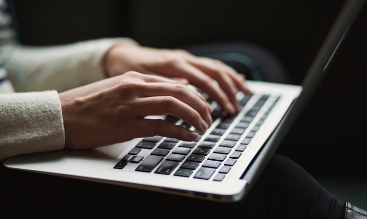 Sachtexte schreiben Headerbild: Nahaufnahme zweier Hände, die auf einem Laptop tippen