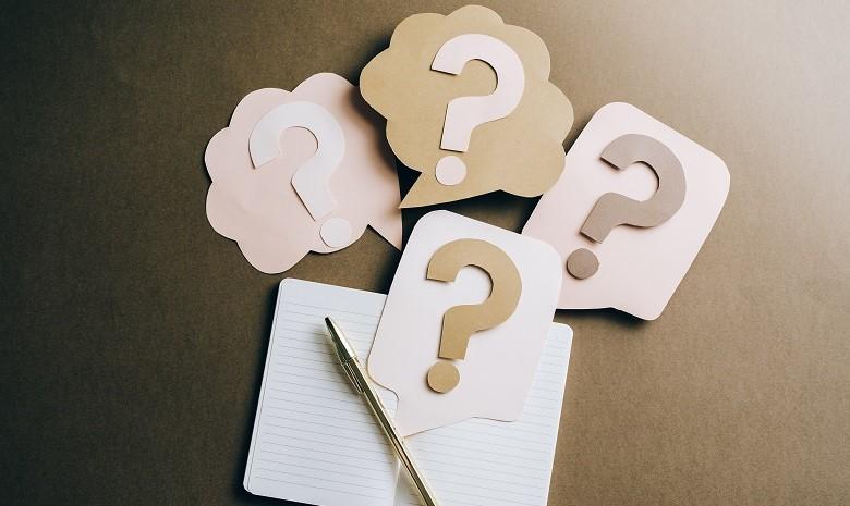 Fachartikel schreiben Beitragsbild 1: Aus Papier ausgeschnittene Fragezeichen liegen verstreut auf einem Notizbuch neben einem goldenen Kugelschreiber.