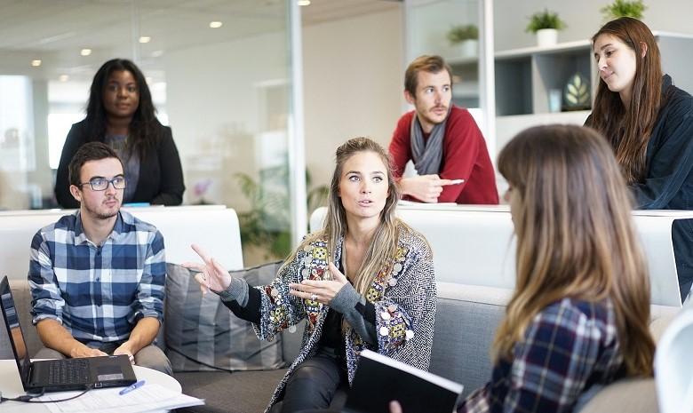 Eine Gruppe junger Menschen sitzt um einen Tisch und diskutiert angeregt.