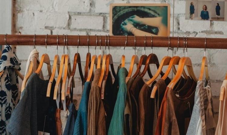 Ein Kleiderständer aus Holz voll bunter Oberteile.
