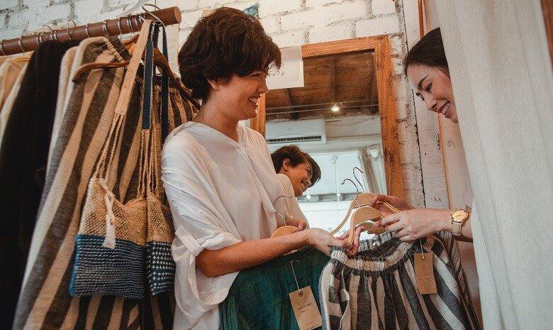Eine Verkäuferin reicht einer Frau in der Umkleide ein Oberteil.