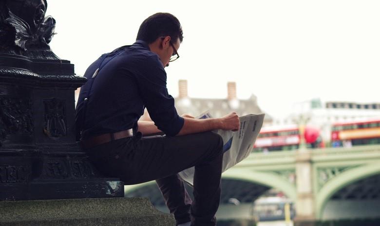 Reportage schreiben Beitragsbild 1: Rückenansicht eines Mannes, der gespannt Zeitung liest.