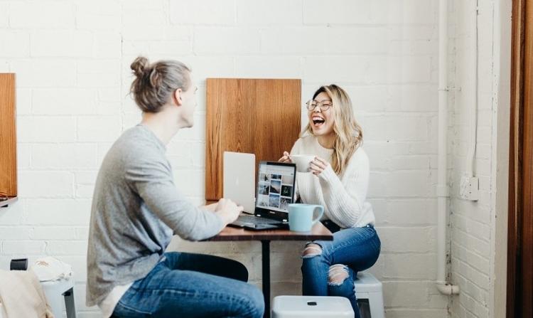 Umgangssprache Headerbild: Eine junge Frau und ein Mann sitzen sich an einem Tisch gegenüber und unterhalten sich angeregt.