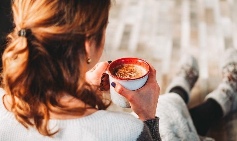 Schreibblockade Beitragsbild Kaffeepause: Rückansicht einer jungen Frau mit Kaffeetasse