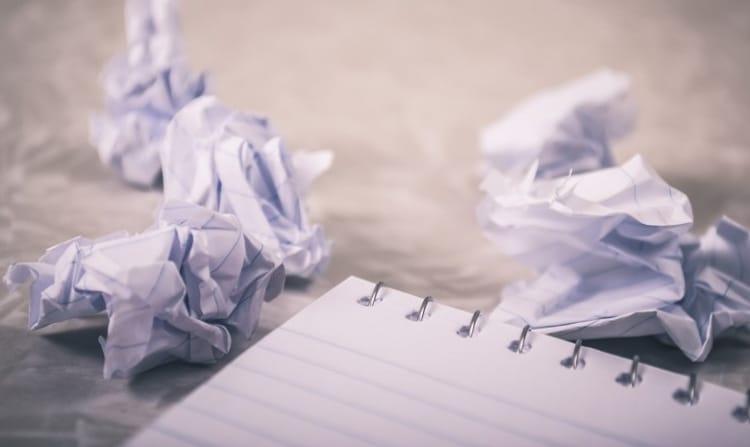 Headerbild Schreibblockade: Zusammengeknüllte Blätter mit Texten und ein leerer Block