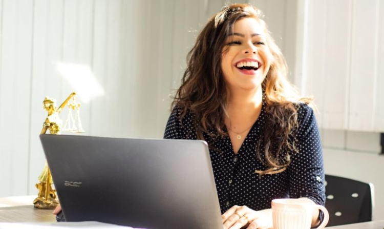 Lachende Frau vor Laptop