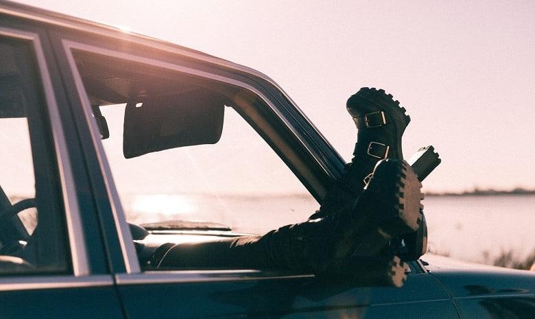 Eine junge Frau sitzt entspannt im Auto und lässt die Füße aus dem Fenster hängen.