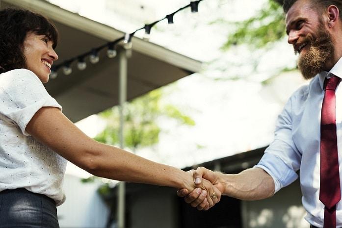 Kunden gewinnen Netzwerken Beitragsbild: Eine junge Frau und ein junger Mann schütteln sich die Hände und lächeln