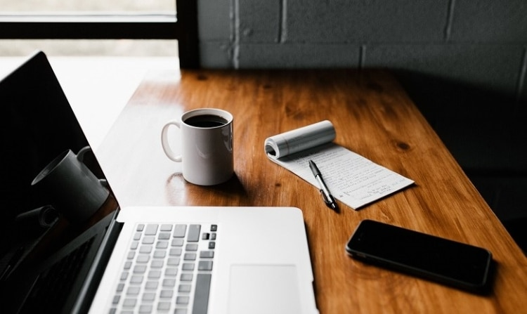 Ansicht eines aufgeklappten Laptops auf einem Schreibitsch, davor liegen ein Handy, ein Notizblock mit Stift und eine volle Kaffeetasse.