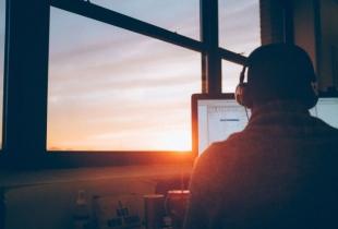 Mann allein an Schreibtisch vor Laptop im Sonnenuntergang