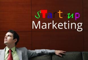 Mann vor Wand mit Headline Start-up Marketing