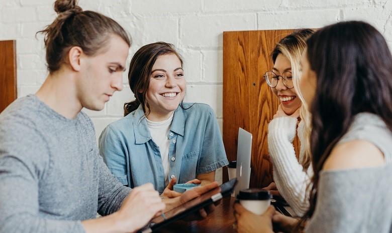 Texter werden Beitragsbild 2: Eine Gruppe von Freunden sitzt an einem Tisch und unterhält sich angeregt