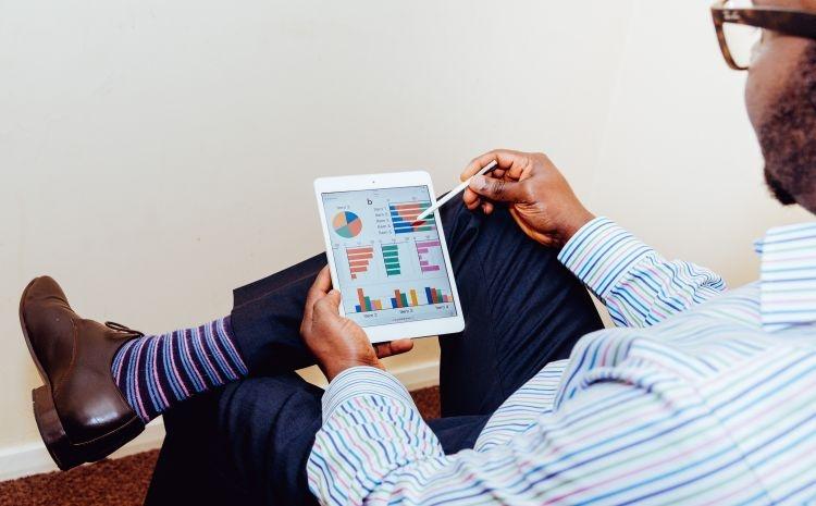 Mann vor Tablet mit Charts