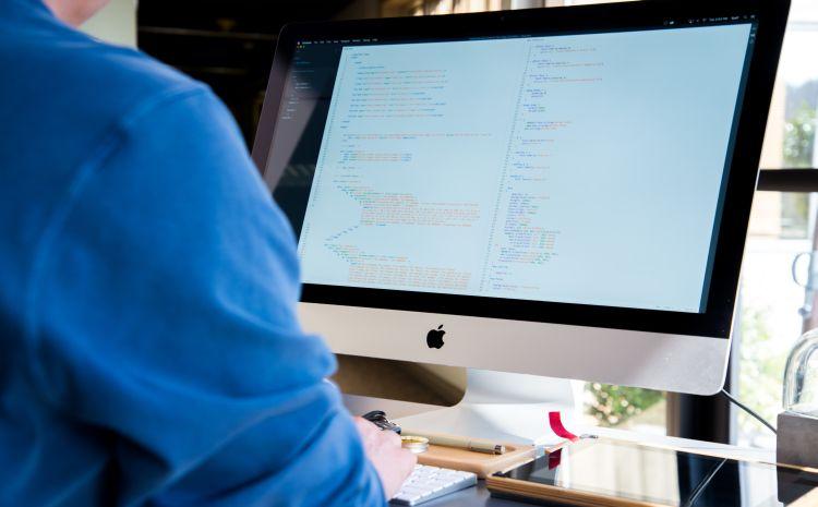 Mann sitzt vor Bildschirm mit Code