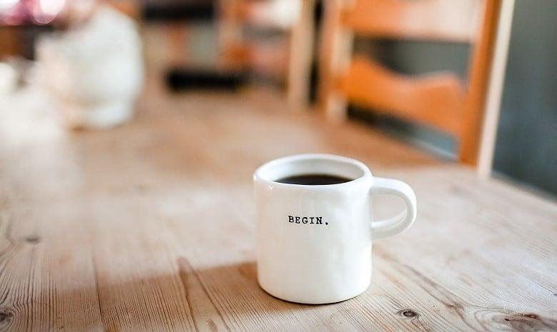 """Textanfang Beitragsbild 1: Eine weiße Tasse, gefüllt mit Kaffee. Auf der Seite der Tasse steht """"Begin"""" (Englisch für Anfangen)"""