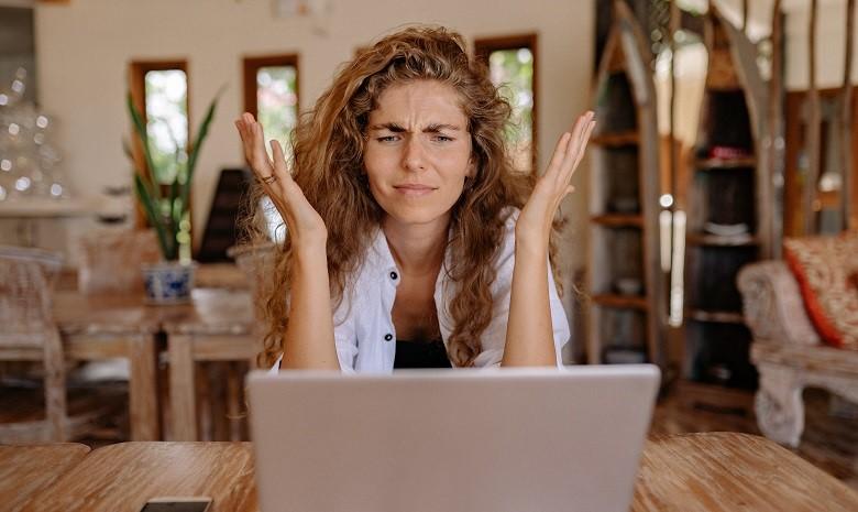 Textanfang Beitragsbild 2: Eine Frau schaut frustriert auf ihren Laptopbildschirm