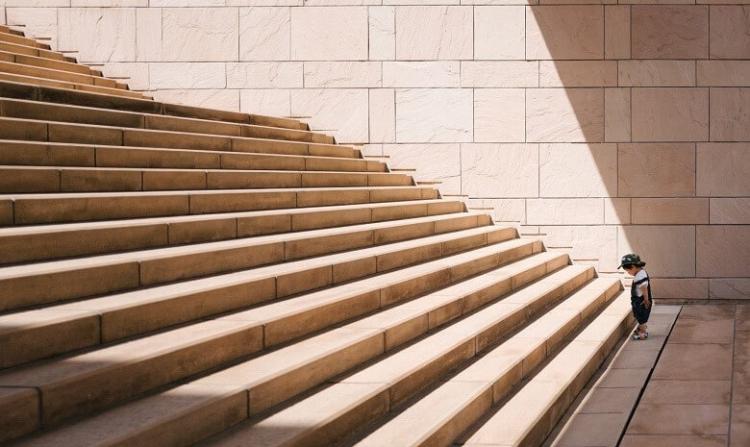 Textanfang Headerbild: Ein kleines Kind steht unten vor einer großen Treppe