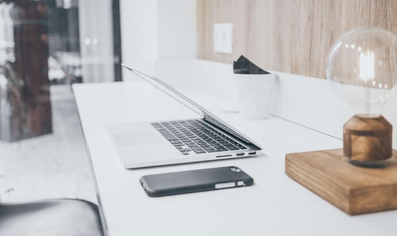 W-Fragen Beitragsbild: Schreibtisch mit Laptop und Glühbirne