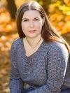 Bild der Autorin Chrysana, Porträt vor unscharfen Bäumen im Hintergrund