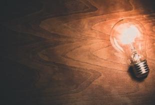 Eine leuchtende Glühbirne auf einem Holztisch